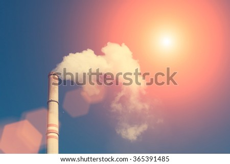 Industrial exhaust pipe with smoke against the sky with reflections of the sun
