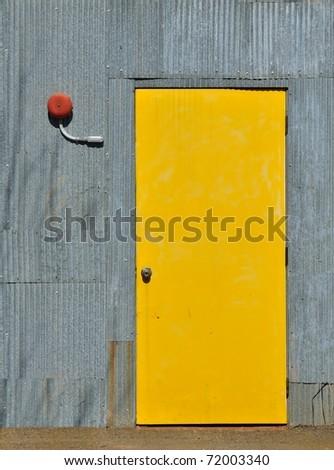 Industrial exterior yellow door with alarm bell - stock photo