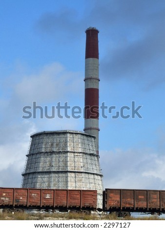 Industrial factory and cargo train. Chimney and a cooling tower. - stock photo
