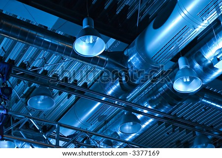 Industrial factory ceiling with ventilation system and lights - stock photo