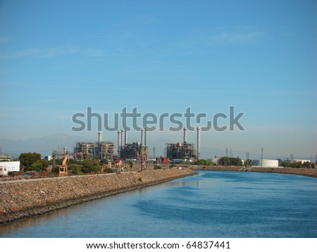 industrial factory in the distance along peaceful river - stock photo