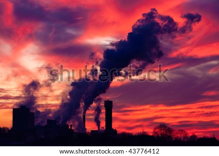 Industrial factory with smoking chimney at sunset