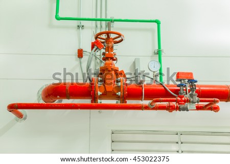 Industrial fire protection system with pressure gauge for measuring pressure, pipeline extinguishing water on the wall.  - stock photo