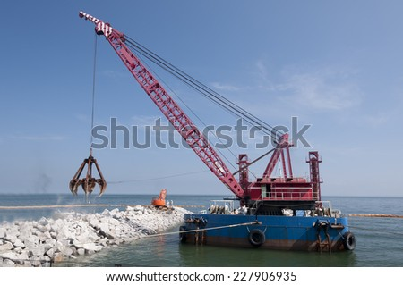 Industrial floating sea crane for carrying the rocks and stones - stock photo