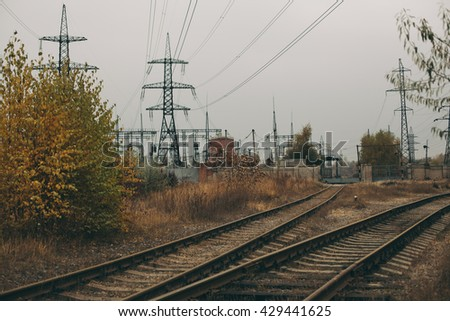 Industrial foggy landscape - old abandoned industrial zone in autumn forest - stock photo