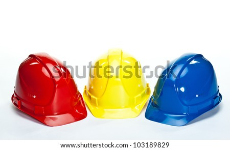 Industrial hardhats on white background; closeup of three multicolored construction hardhats - stock photo