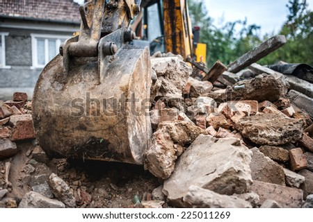 industrial hydraulic backhoe bulldozer loading demolition debris, stone and concrete for recycling - stock photo