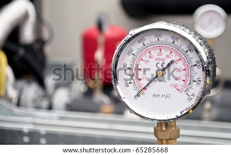 Industrial hydraulic round barometer with rain over it - stock photo