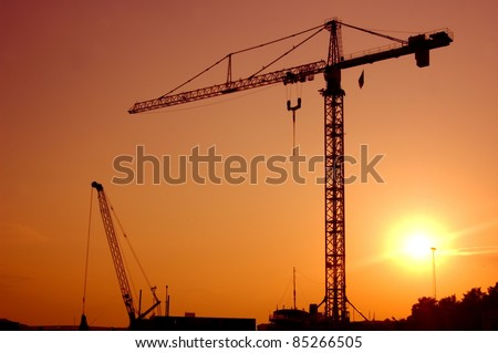 Industrial landscape. Construction cranes against sunset. - stock photo