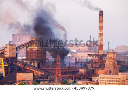 Industrial landscape in Ukraine. Steel factory with smog at sunset. Pipes with smoke. Metallurgical plant. steelworks, iron works. Heavy industry. Ecology problems, atmospheric pollutants. - stock photo
