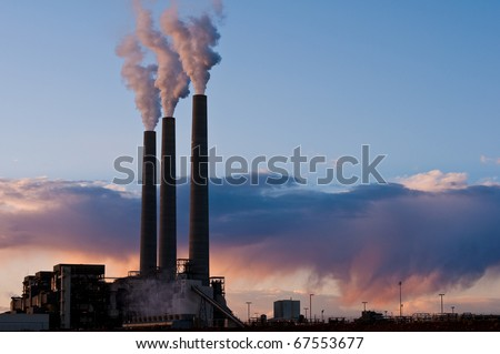 industrial landscape of coal burning smoke stacks and sunset sky - stock photo