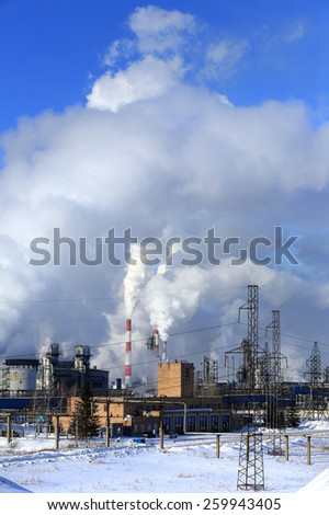industrial landscape smoke from the chimneys large plant and power lines against the blue sky in winter