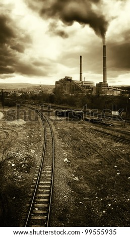 industrial landscape with railroad and toxic fumes coming from high towers polluting the air - stock photo