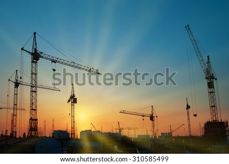 Industrial landscape with silhouettes of cranes over sunset - stock photo