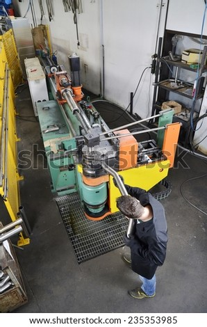 Industrial machine for the bending of pipes with operator at work in metal warehouse. Construction of a homemade muffler for sportive cars in stainless steel.