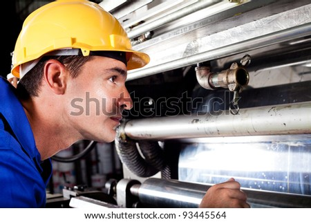 industrial machine operator checking on machine while it's running - stock photo