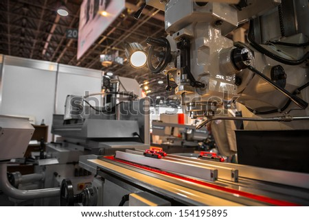 Industrial machines working for the weak humans in a factory - stock photo
