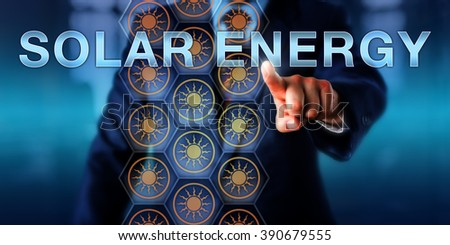 Industrial manager presses SOLAR ENERGY on a touch screen interface. Business metaphor and ever evolving technology concept for industrial scale solutions to convert solar energy into electric power. - stock photo