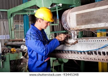 industrial mechanic repairing heavy industry machine in plant - stock photo