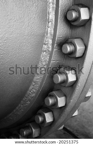 Industrial metallic pipeline joint with many screws and bolts - stock photo