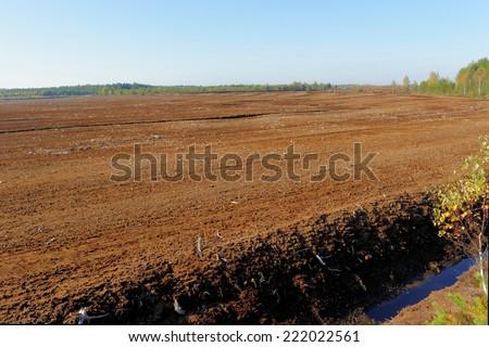 Industrial milled peat production in Saara bog, Estonia. - stock photo