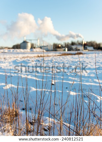 industrial park with chimney and white smoke on blue sky - stock photo