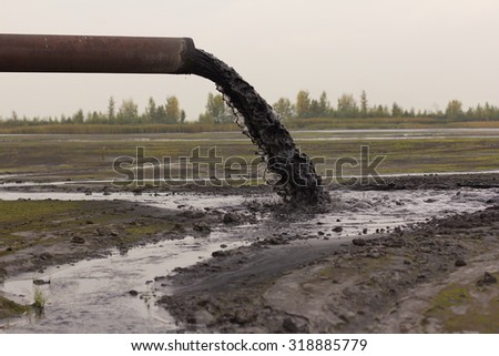 Industrial pipe discharging liquid waste - stock photo