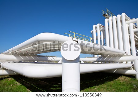 Industrial pipe with gas and oil and water on a background of blue sky - stock photo