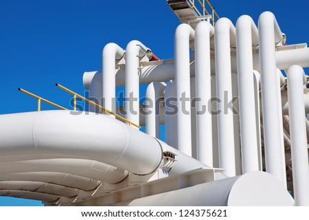 Industrial pipe with gas and oil and water on a background of blue sky