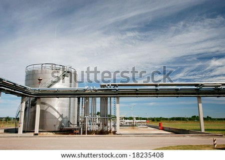 industrial pipelines and storage tank against blue sky