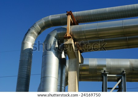 industrial pipelines and storage tanks against blue sky - stock photo