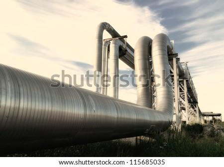 industrial pipelines on pipe-bridge against blue sky - stock photo