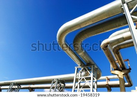 industrial pipelines on pipe-bridge against blue sky. - stock photo