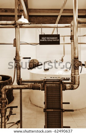 Industrial pipes and equipment in whisky distillery - stock photo