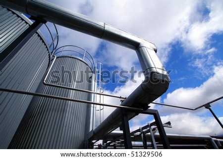 industrial piping and tanks against blue sky - stock photo
