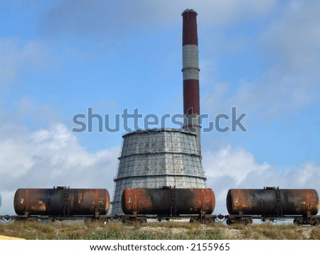 Industrial plant chimney and cooling tower and train tank carriages. - stock photo