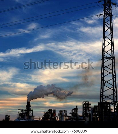 Industrial plant exhausting dangerous smokes into the atmosphere. - stock photo