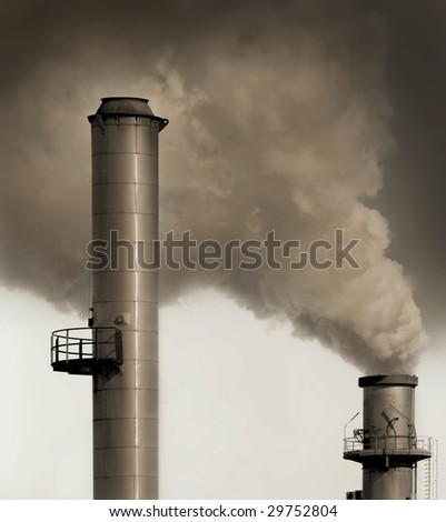 Industrial plant exhausting smokes into the atmosphere. - stock photo
