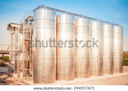 Industrial plant for storing wine, with stainless steel containers, at the sunset sun