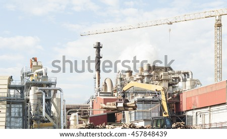 industrial plant of a furniture factory with smoking smokestacks,tubes,silos,crane and trunks. - stock photo