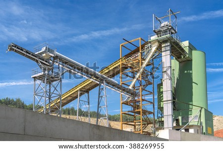 Industrial plant of a quarry in front of blue and white sky  - stock photo