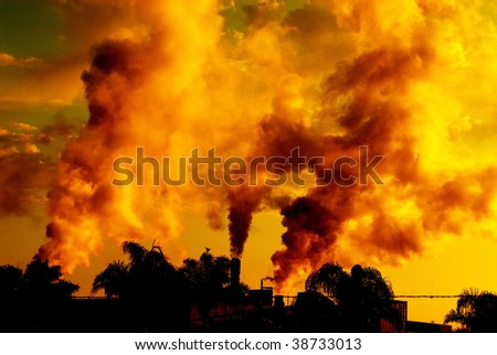industrial plant releasing polluting smoke photographed at sunset - stock photo