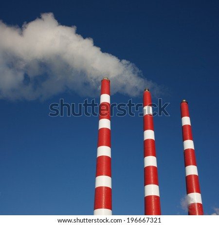 Industrial plant smoke stacks and blue sky.