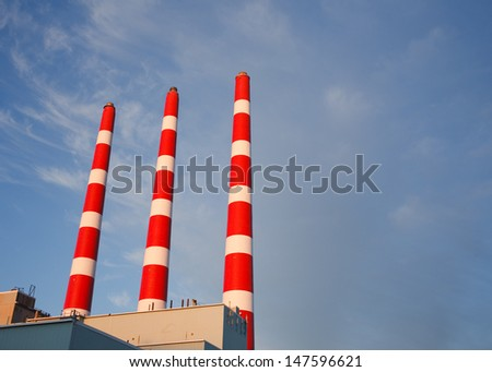 Industrial plant stacks with partially cloudy sky - stock photo