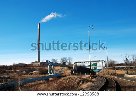 Industrial plant with pipes leading to chimney and railroad - stock photo