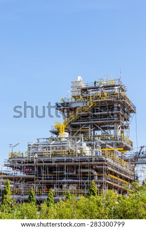 Industrial plants are currently under construction with cranes and worker - stock photo