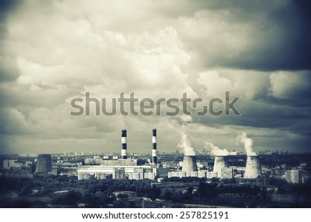 Industrial plants with smoking chimneys in the city - stock photo