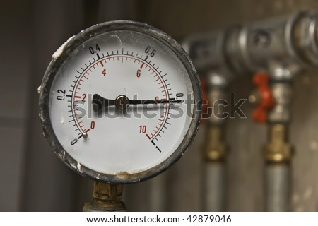 Industrial pressure meter - barometer and water pipes in the background - stock photo