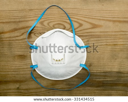 Industrial respirator with valve protects against dust over wooden background - stock photo