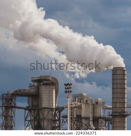 industrial scene with chimneys and stormy sky - stock photo